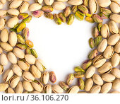 roasted nuts on a whiroasted salted pistachio nuts on a white background and place for inscription in form of heartte background and place for inscription. Стоковое фото, фотограф Татьяна Яцевич / Фотобанк Лори