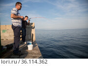 """Croatia, Lovran - Fishermen in Lovran at the Adriatic Sea (Kvarner Bay)"" (2016 год). Редакционное фото, агентство Caro Photoagency / Фотобанк Лори"