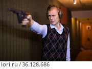 Man aiming smallbore sporting pistol at target in shooting range. Стоковое фото, фотограф Яков Филимонов / Фотобанк Лори