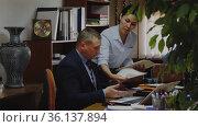 Asian woman assistant with report standing near her successful adult male boss in office. Стоковое видео, видеограф Яков Филимонов / Фотобанк Лори