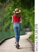 Rear view of casual female tourist riding urban electric scooter in beautiful natural enviorment by lake Bled, Slovenia. Стоковое фото, фотограф Matej Kastelic / Фотобанк Лори