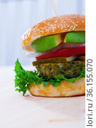 Vegetarian hamburger with soybean patty, fresh vegetables and avocado at plate. Стоковое фото, фотограф Яков Филимонов / Фотобанк Лори