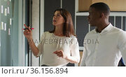 Diverse businessman and businesswoman discussing by whiteboard in modern office. Стоковое видео, агентство Wavebreak Media / Фотобанк Лори