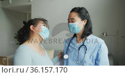 Asian female nurse and patient wearing face masks talking and looking to camera in hospital. Стоковое видео, агентство Wavebreak Media / Фотобанк Лори
