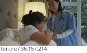 Smiling asian female doctor helping female patient in bed take her medication. Стоковое видео, агентство Wavebreak Media / Фотобанк Лори
