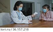 Asian female nurse wearing face mask taking temperature of female patient wearing mask in hospital. Стоковое видео, агентство Wavebreak Media / Фотобанк Лори