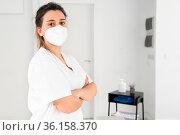 Confident female physiotherapist posing in modern clinic wearing protective... Стоковое фото, фотограф Zoonar.com/DAVID HERRAEZ CALZADA / easy Fotostock / Фотобанк Лори