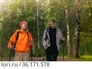 Two teenage girls are trekking in the forest with nordic walking poles. Стоковое фото, фотограф Евгений Харитонов / Фотобанк Лори