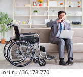 Disabled businessman on wheelchair working from home. Стоковое фото, фотограф Elnur / Фотобанк Лори