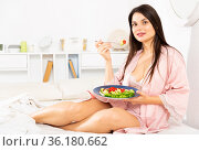 Woman in bathrobe holding fork and eating vegetable salad in bed. Стоковое фото, фотограф Яков Филимонов / Фотобанк Лори