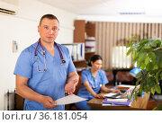 Professional doctor standing in office with patient medical history. Стоковое фото, фотограф Яков Филимонов / Фотобанк Лори