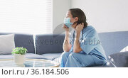 Caucasian female doctor wearing face mask at home sitting on couch. Стоковое видео, агентство Wavebreak Media / Фотобанк Лори