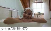 Portrait of mixed race woman taking a bath looking at camera. Стоковое видео, агентство Wavebreak Media / Фотобанк Лори