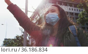 Asian woman wearing face mask hailing a taxi while standing on the street. Стоковое видео, агентство Wavebreak Media / Фотобанк Лори