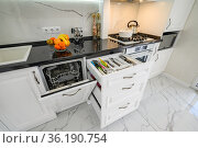 Luxurious white modern kitchen interior, drawers pulled out, dishwasher's door open, high angle. Стоковое фото, фотограф Сергей Старуш / Фотобанк Лори