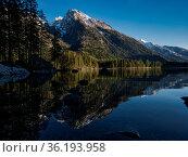 Eine Bergspitze spiegelt sich im klaren Wasser vom Hintersee in Berchtesgaden... Стоковое фото, фотограф Zoonar.com/Christian Länger / easy Fotostock / Фотобанк Лори