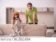 Young man sitting on the sofa with female skeleton. Стоковое фото, фотограф Elnur / Фотобанк Лори