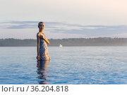 Teen girl in a dress standing in the water. Стоковое фото, фотограф Евгений Харитонов / Фотобанк Лори