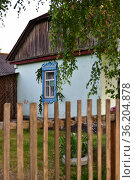 Typical rural house with platbands and wooden fence in Russia. Стоковое фото, фотограф Володина Ольга / Фотобанк Лори