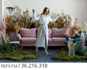 Nice young woman in a room with sofa in the middle of tall grass. Стоковое фото, фотограф Алексей Кузнецов / Фотобанк Лори