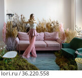Pleasant young woman dancing in a room with sofa in the middle of tall grass. Стоковое фото, фотограф Алексей Кузнецов / Фотобанк Лори