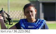 Portrait of happy caucasian female baseball player on field, taking helmet off and smiling. Стоковое видео, агентство Wavebreak Media / Фотобанк Лори