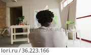 Rear view of thoughtful african american male artist sitting looking at his painting at art studio. Стоковое видео, агентство Wavebreak Media / Фотобанк Лори