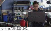 Female mechanic using laptop and inspecting the car at a car service station. Стоковое видео, агентство Wavebreak Media / Фотобанк Лори