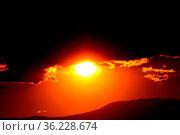 Wie ein Auge wirkt die untergehende Sonne zwischen den Wolken und... Стоковое фото, фотограф Zoonar.com/Joachim Hahne / age Fotostock / Фотобанк Лори
