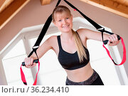 Happy girl in sling training at home. Стоковое фото, фотограф Zoonar.com/Wolfgang Zwanzger www.20er.net / easy Fotostock / Фотобанк Лори