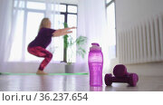 Fitness training - overweight woman squatting on the yoga mat then walks to a bottle of water and pick it up. Стоковое видео, видеограф Константин Шишкин / Фотобанк Лори