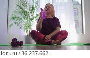 Fitness training - blonde overweight woman sitting on yoga mat and puts on her wireless headphones. Стоковое видео, видеограф Константин Шишкин / Фотобанк Лори