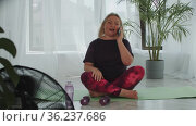 Blonde overweight woman doing fitness exercises with dumbbells then takes her phone and answers the call. Стоковое видео, видеограф Константин Шишкин / Фотобанк Лори