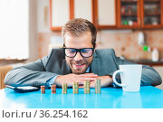 Working from home. Young businessman checking on returns from his... Стоковое фото, фотограф Zoonar.com/Tomas Anderson / easy Fotostock / Фотобанк Лори