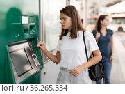 Woman using ticket vending machine at tram stop. Стоковое фото, фотограф Яков Филимонов / Фотобанк Лори