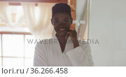 Portrait of african american attractive woman in white robe looking at camera and smiling. Стоковое видео, агентство Wavebreak Media / Фотобанк Лори
