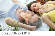 Beautiful old grandmother with grey hair and face with wrinkles is lying on white carpet with her adult daughter on green grass during picnic outdoors, mother's day, happy retirement. Стоковое видео, видеограф Ольга Балынская / Фотобанк Лори