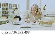 Mature teacher engaged in a public library. Стоковое видео, видеограф Яков Филимонов / Фотобанк Лори