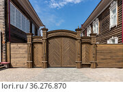 Magnificent carved wooden gates between houses on Gorky Street, improvement of the historical center of the city. Russia, Krasnoyarsk, June 9, 2021. Редакционное фото, фотограф ok_fotoday / Фотобанк Лори