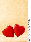 Two red handmade wooden hearts on golden bright glitter lights bokeh... Стоковое фото, фотограф Zoonar.com/Ivan Mikhaylov / easy Fotostock / Фотобанк Лори