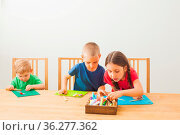 Adorable girl with two braids and two cute boys modeling from playdough... Стоковое фото, фотограф Zoonar.com/Oksana Shufrych / easy Fotostock / Фотобанк Лори