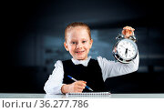 Smiling little girl holding alarm clock. Time to study and back to... Стоковое фото, фотограф Zoonar.com/Aleksandr Khakimullin / easy Fotostock / Фотобанк Лори