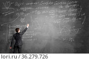 Man in suit standing with back and drawing formulas on chalkboard. Стоковое фото, фотограф Zoonar.com/Aleksandr Khakimullin / easy Fotostock / Фотобанк Лори