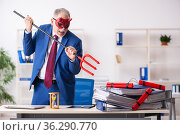 Old male devil employee with dynamite in the office. Стоковое фото, фотограф Elnur / Фотобанк Лори