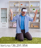 Man with virtual reality glasses playing at home. Стоковое фото, фотограф Elnur / Фотобанк Лори