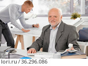 Senior businessman sitting at desk, smiling at camera, young architect... Стоковое фото, фотограф Zoonar.com/StockLite / easy Fotostock / Фотобанк Лори