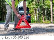 An adult man places a reflective red triangular warning triangle. Стоковое фото, фотограф Ольга Губская / Фотобанк Лори