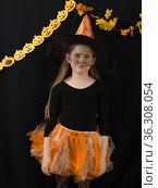 Веселая девочка школьного возраста в костюме ведьмы на черном фоне. Праздник Halloween. Стоковое фото, фотограф Наталья Гармашева / Фотобанк Лори