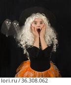 Девочка школьного возраста в белом парике и костюме ведьмы в ужасе или удивлении схватилась руками за лицо. Стоковое фото, фотограф Наталья Гармашева / Фотобанк Лори
