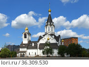 Snow white church of Holy Apostles Constantine and Elena against blue sky with white clouds. Редакционное фото, фотограф Валерия Попова / Фотобанк Лори